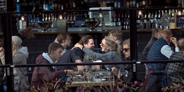 FILE - In this Saturday, April 4, 2020 file photo a couple hug and laugh as they have lunch in a restaurant in Stockholm, Sweden. (AP Photo/Andres Kudacki, File)