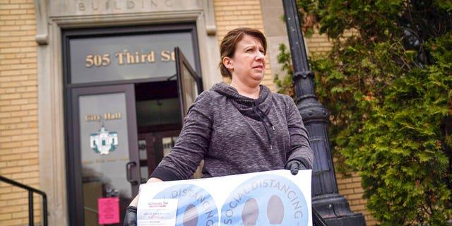 Hudson, Wis., city clerk Becky Eggen displays some of the health alert and social distancing signs. (Glen Stubbe/Star Tribune via AP)