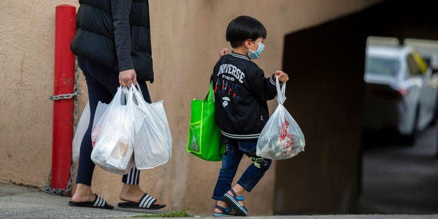An adult and a child, both wearing face masks amid the coronavirus outbreak, carry bags in the Chinatown neighborhood of Los Angeles, Calif., on April 2, 2020.(AP Photo/Damian Dovarganes, File)