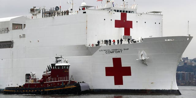 In this March 30, 2020 file photo, the U.S. Navy hospital ship USNS Comfort is escorted up the Hudson River on its way to New York City. On Tuesday, April 21, 2020, while expressing confidence that stresses on New York City's hospital system are easing, New York Gov. Andrew Cuomo said that the ship deployed to New York City to help fight the coronavirus outbreak is no longer needed.