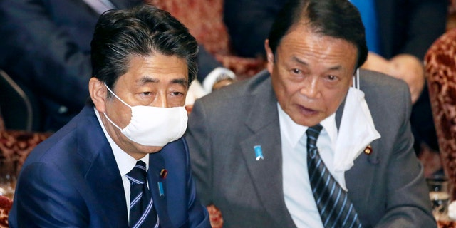 Japanese Prime Minister Shinzo Abe, left, and Financial Minister Taro Aso, wear face masks as a safety precaution against the new coronavirus attend a session of the parliament's upper house in Tokyo Wednesday.