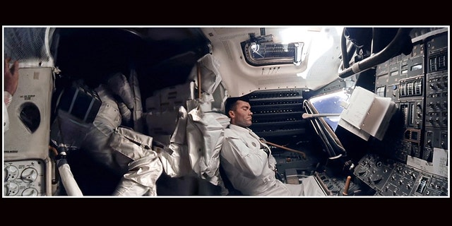 The panoramic hi-def image of interior of the Apollo 13 Lunar Module. Astronaut Fred Haise (right) is napping, while Jack Swigert can be seen curled up in the storage area. Commander Jim Lovell's hand can be seen in the left of the picture.