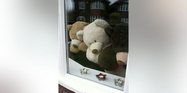 The woman's children have helped her arrange the bears for fun.