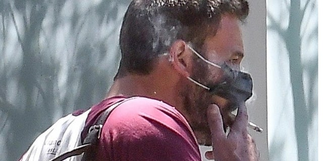 Ben Affleck was spotted smoking a cigarette with his protective mask partially off.
