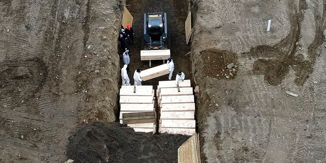 Workers wearing personal protective equipment bury bodies in a trench on Hart Island in New York City's Bronx borough on Thursday. (AP)
