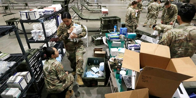 Soldiers unload supplies as they work to set up a field hospital inside CenturyLink Field Event Center on Tuesday. (AP Photo/Elaine Thompson)