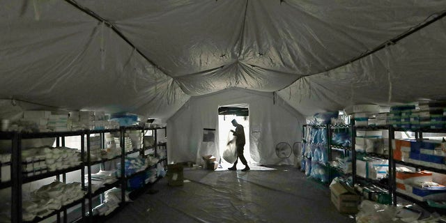 A U.S. Army soldier walks inside a mobile surgical unit being set up by soldiers as part of a field hospital inside CenturyLink Field Event Center on Tuesday. (AP Photo/Elaine Thompson)