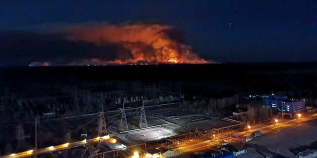 In this photo taken from the roof of Ukraine's Chernobyl nuclear power plant late Friday April 10, 2020, a forest fire is seen burning near the plant inside the exclusion zone.