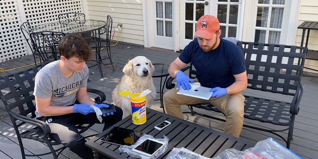 Sam and Ben Hitt sanitize donated iPads outside their house, with dog Abby observing.