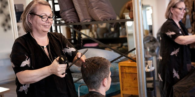 Christel Lerche cuts a customer's hair at Hot N Tot Hairdressers, in Bagsvaerd, Denmark, Monday, April 20, 2020. Denmark began reopening hair salons, dentists, physiotherapists, tattoo parlors and driving schools, among others on Monday which had previously been closed amid the coronavirus pandemic. (Liselotte Sabroe/Ritzau Scanpix via AP)