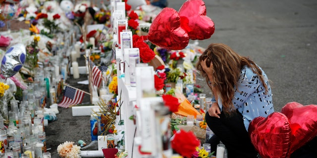 FILE - In this Aug. 6, 2019, file photo, Gloria Garces kneels in front of crosses at a makeshift memorial near the scene of a mass shooting at a shopping complex in El Paso, Texas. A hospital official said Sunday, April 26, 2020, that a man shot in the Aug. 3 attack targeting Latinos in an El Paso Walmart has died after months in the hospital. (AP Photo/John Locher, File)