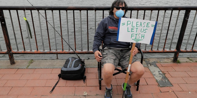 "Ray Kawabata holds a sign that reads ""Please Let Us Fish"" at Gas Works Park in Seattle on April 26, during a protest against Washington state's current ban on fishing due to stay-at-home orders implemented to prevent the spread of the coronavirus. (AP Photo/Ted S. Warren)"