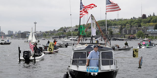A protester reels in a fake fish near poles marking a six-foot social distance on a boat on Lake Union near Gas Works Park in Seattle on April 26. (AP Photo/Ted S. Warren)