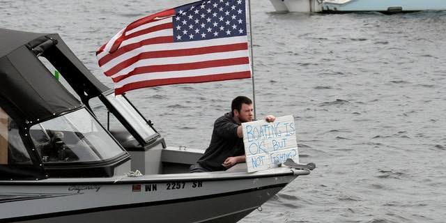 "A protester hold a sign that reads ""Boating is OK, but Not Fishing?"" as he sits on a boat on Lake Union near Gas Works Park in Seattle on April 26. (AP Photo/Ted S. Warren)"