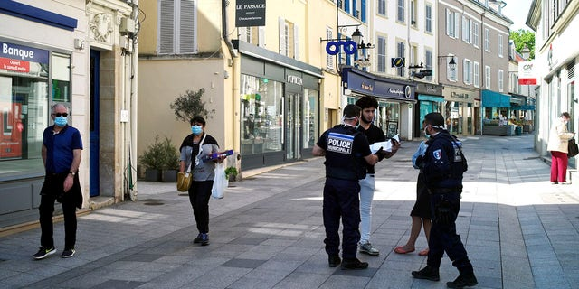 Municipal police officers check documents as they patrol in a street of Sceaux during nationwide confinement measures to counter the Covid-19. (AP Photo/Thibault Camus)