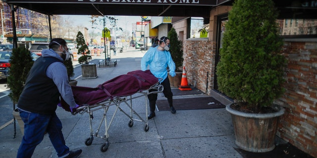 Employees deliver a body at Daniel J. Schaefer Funeral Home, Thursday, April 2, 2020, in the Brooklyn borough of New York City. The company is equipped to handle 40-60 cases at a time. But amid the coronavirus pandemic, it was taking care of 185 Thursday morning. (AP Photo/John Minchillo)
