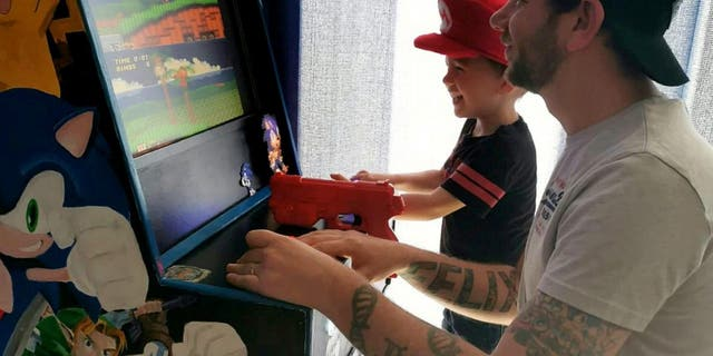 Steve Addison, who works as an assistant manager at McDonalds, found himself at a loose end after being put on furlough leave. But rather than stew around the house all day, the 32-year-old decided to finish off a plan to dig out an Atari he got as a Christmas gift and create a cabinet so he and three-year-old son Felix could play on it. (Credit: SWNS)