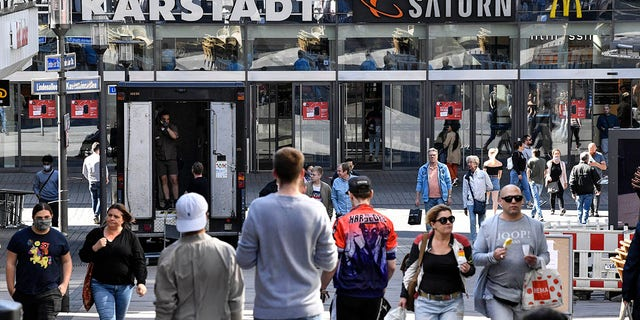 People walk to a shopping center as many smaller stores are allowed to open in Essen, Germany, Monday, April 20, 2020. Europe's biggest economy starts reopening some of its stores and factories after weeks of lockdown due to the new coronavirus outbreak. (AP Photo/Martin Meissner)