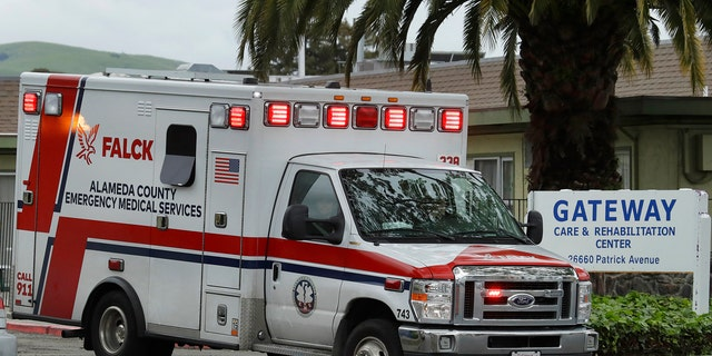 An ambulance leaves the Gateway Care and Rehabilitation Center on Thursday. At least 13 patients at the facility have died of coronavirus, and 41 others have been infected.