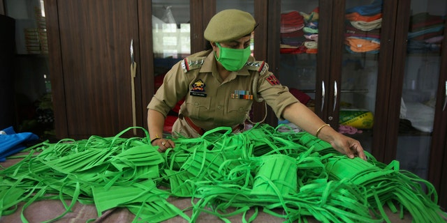 An officer checks the quality as Jammu and Kashmir police personnel make face masks and personal protective gear amid COVID-19 outbreak in Jammu, India, Wednesday.