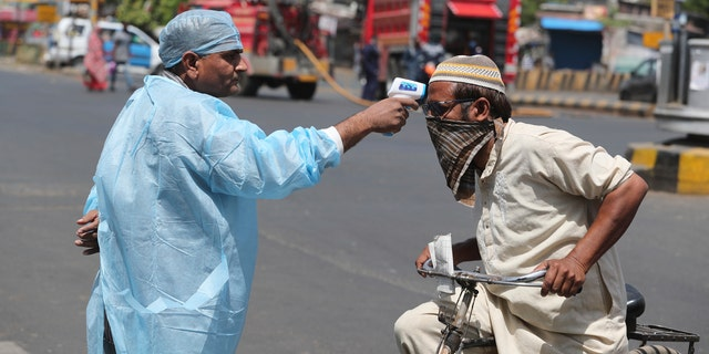 An Indian health worker checks the temperature of a man during lockdown to prevent the spread of new coronavirus in Ahmedabad, India, Wednesday.