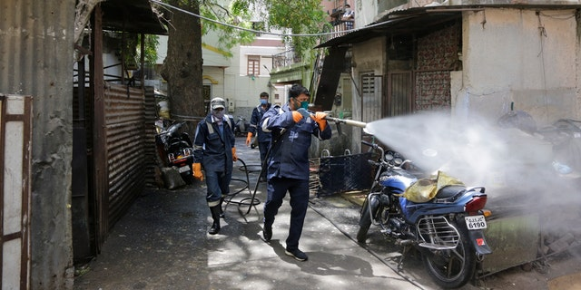 Fire service personnel spray disinfectant in a residential area during lockdown to prevent the spread of new coronavirus in Ahmedabad, India, Wednesday.