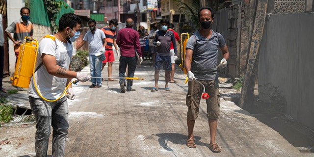 Residents sanitize their area as a preventive measure against the COVID-19 in Gauhati, India, Sunday, April 5, 2020.