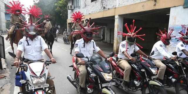 Indian policeman wearing virus themed helmets ride on motorcycles during an awareness rally aimed at preventing the spread of new coronavirus in Hyderabad, India, Thursday, April 2, 2020.