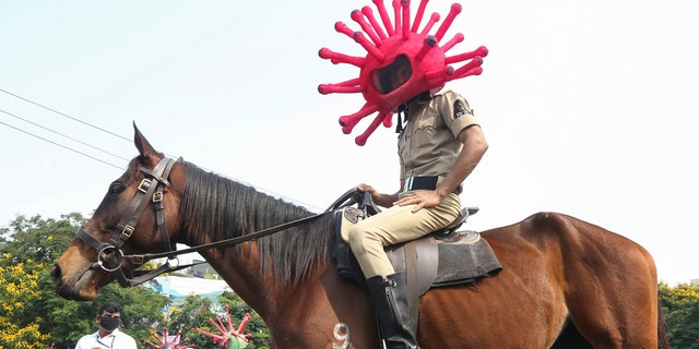 An Indian policeman wearing a virus themed helmet rides on a horse during an awareness rally aimed at preventing the spread of new coronavirus in Hyderabad, India, Thursday, April 2, 2020.
