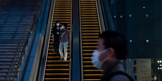 Wearing protective masks to help reduce the spread of the coronavirus, commuters ride an escalator Monday, April 6, 2020, in Tokyo.
