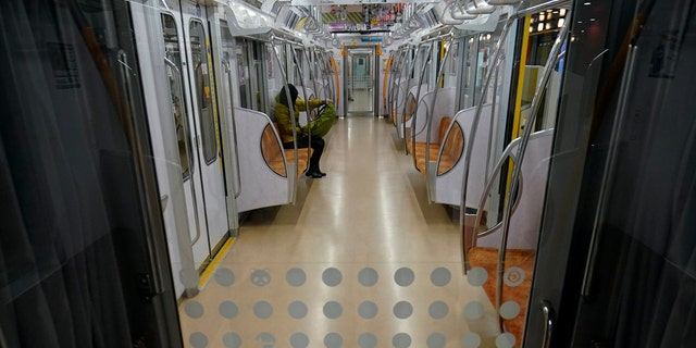 A woman rides an empty subway Monday, April 13, 2020, in Tokyo.