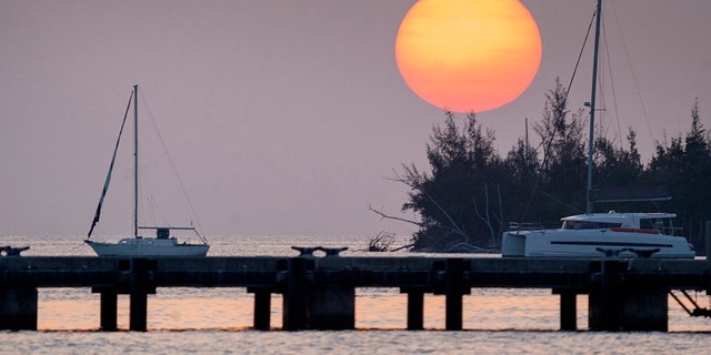 The sun sets Friday, April 17, 2020, over a quiet Key West Harbor in Key West, Fla. Gov. Ron Desantis opened Florida beaches Friday as a first move to reopen the state after the coronavirus outbreak. (Rob O'Neal/The Key West Citizen via AP)