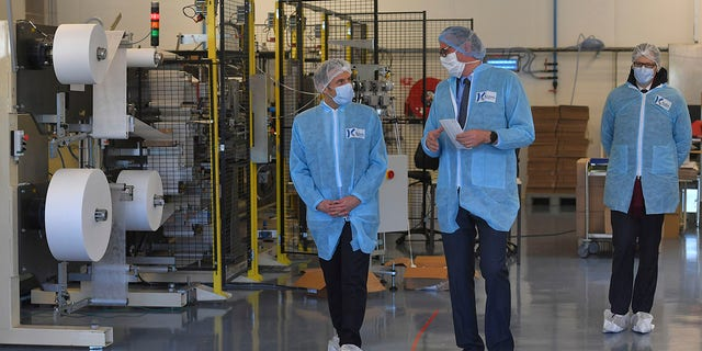 Macron, left, wearing protective suit and a face mask, visits the Kolmi-Hopen protective face masks factory in Saint-Barthelemy-d'Anjou near Angers, central France, on Tuesday. (Loic Venance, Pool via AP)