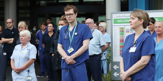Staff stand outside Salford Royal Hospital in Manchester, England, Tuesday April 28, 2020, during a minute's silence to pay tribute to the NHS staff and key workers who have died during the coronavirus outbreak. (Peter Byrne/PA via AP)
