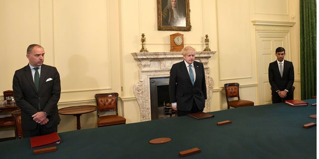 Britain's Prime Minister Boris Johnson, center, Chancellor of the Exchequer Rishi Sunak, right, and Cabinet Secretary Mark Sedwill stand inside 10 Downing Street, London, Tuesday April 28, 2020, during a minute's silence to pay tribute to the NHS staff and key workers who have died during the coronavirus outbreak. (Stefan Rousseau/PA via AP)