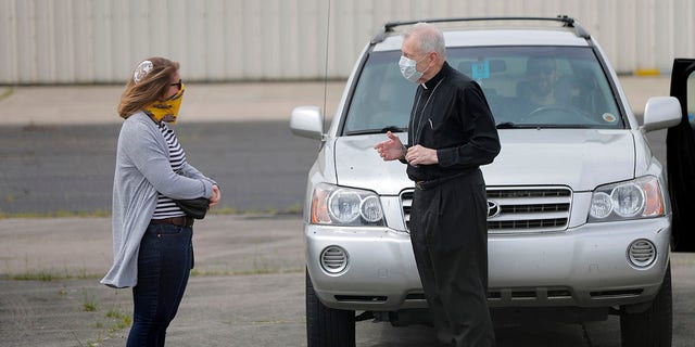 Aymond talks with Rabbi Lexi Erdheim after he flew over the city to bless victims of the coronavirus. Erdheim flew next and gave blessings for those affected by the virus during Passover. (AP Photo/Gerald Herbert)