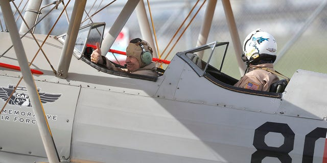 Archbishop Gregory Aymond, left, gives a thumbs-up as he gets set to ride in a World War II-era Stearman PT-17 biplane over the city on Friday. (AP Photo/Gerald Herbert)