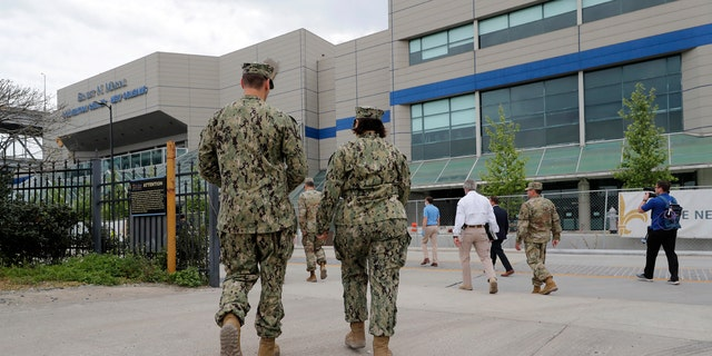 National Guard personnel walk outside the Ernest N. Morial Convention Center during a media tour of a temporary hospital that has been set up, as an overflow for local hospitals that are reaching capacity, in response to the COVID-19 pandemic, in New Orleans.