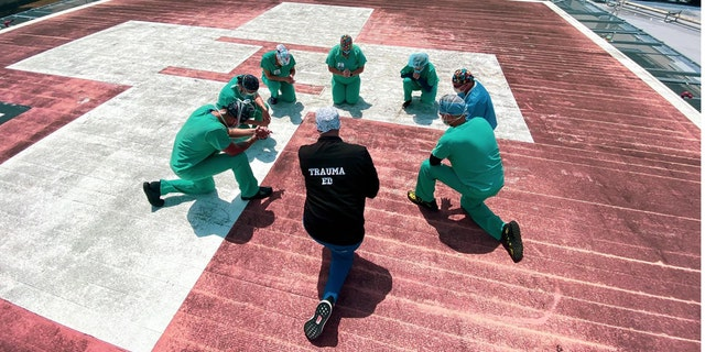 Hospital staff at Jackson South Medical Center pray on the hospital's helipad.
