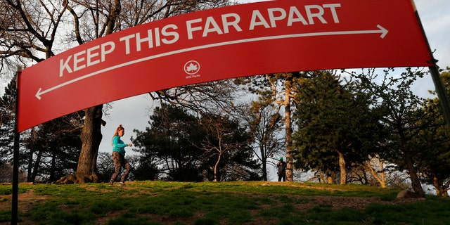 A woman jogs in Brooklyn's Fort Greene Park, Sunday, April 5, 2020, beneath a sign demonstrating the distance people should keep from each other during the coronavirus outbreak in New York.