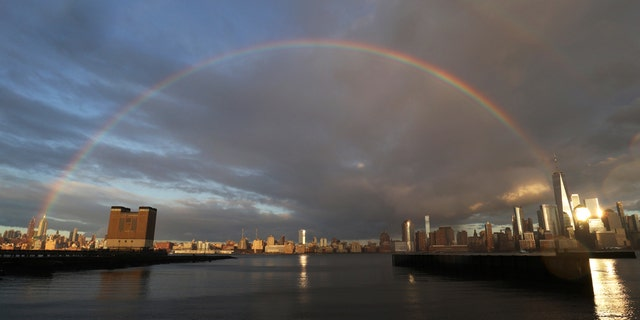 A rainbow forms in the sky from the top of One World Trade Center to the top of the Empire State Building as the sun sets in New York City on April 13, 2020, as seen from Jersey City, N.J.