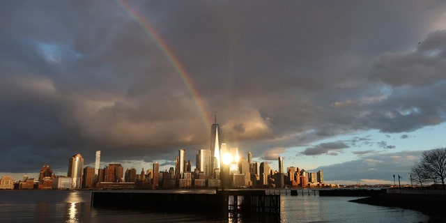 The rainbow forms in the sky over One World Trade Center and lower Manhattan as the sun sets in New York City on April 13, 2020, as seen from Jersey City, N.J.