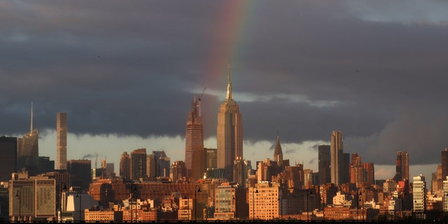 A rainbow forms in the sky over the Empire State Building and midtown Manhattan as the sun sets in New York City on April 13, 2020, as seen from Jersey City, New Jersey. (Photo by Gary Hershorn/FOX News)