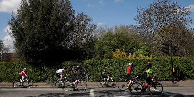 Cyclists spread out as they observe social distancing whilst waiting at a traffic light by Regent's Park, London, as London's parks remain open with the warning that they will close if people fail to observe the British government guidelines.