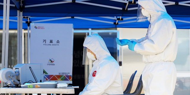 Election officials wearing protective gears, wait for voters during an early voting for the April 15 general elections at a special polling station set up for coronavirus patients and medical members at a treatment center in Yongin, South Korea.