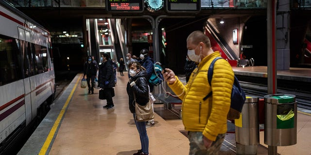 Commuters wearing face masks to protect against coronavirus at the platform of Atocha train station in Madrid, Spain, Monday, April 13, 2020. Confronting both a public health emergency and long-term economic injury, Spain is cautiously re-starting some business activity to emerge from the nationwide near-total freeze that helped slow the country's grim coronavirus outbreak. (AP Photo/Bernat Armangue)