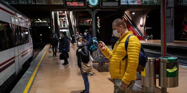 Commuters wearing face masks to protect against coronavirus wait at the platform of Atocha train station in Madrid on Monday. (AP Photo/Bernat Armangue)