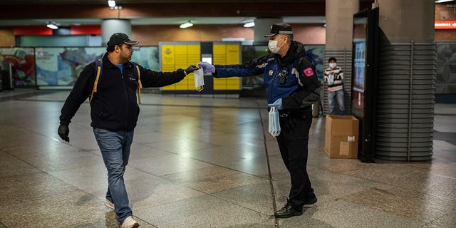 A local police officer distributes face masks to commuters at the Atocha train station during the coronavirus outbreak in Madrid on Monday. (AP Photo/Bernat Armangue)