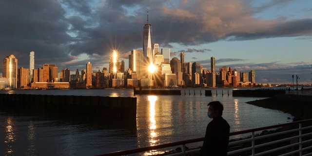 A person in a medical mask watches the sun set on the skyline of lower Manhattan and One World Trade Center in New York City on April 13, 2020 as seen from Jersey City, N.J.