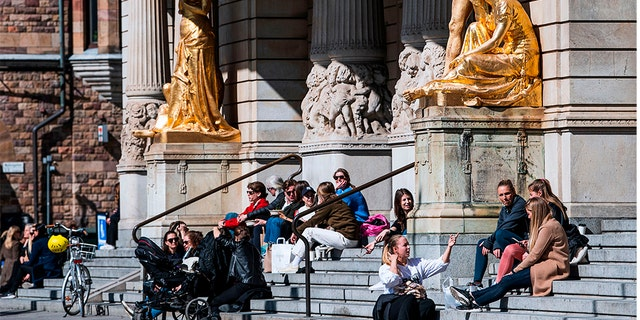 People sit and enjoy the spring weather outside the Royal Dramatic Theatre in Stockholm on April 15, 2020, during the coronavirus COVID-19 pandemic. (Photo by Jonathan NACKSTRAND / AFP) (Photo by JONATHAN NACKSTRAND/AFP via Getty Images)